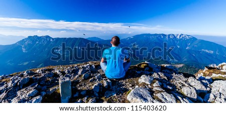 Young man sitting on a cliff's edge on wide alley background. Velika Raduha, Slovenia. - stock photo