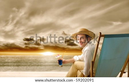 Young man sitting on a deckchair in front of the sea and holding a glass of cocktail - stock photo