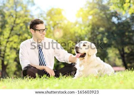Young man sitting on a green grass next to a labrador retriever dog in a park