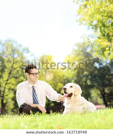 Young man sitting on a green grass next to a labrador retriever dog in a park on a sunny day, shot with a tilt and shift lens