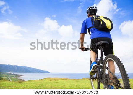 young man sitting on a  mountain bike and looking the ocean - stock photo