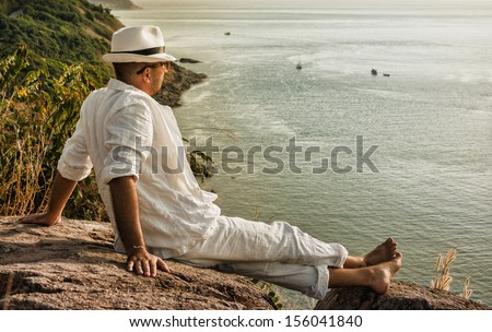 young man sitting on a rock and looking at the sunset of Phuket