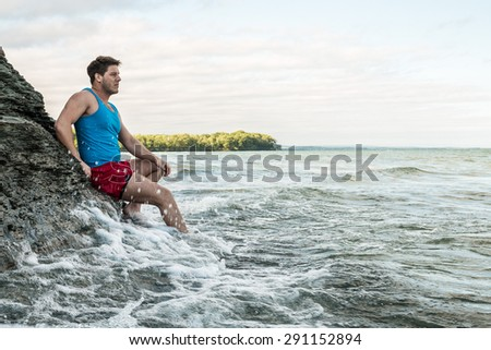 Young man sitting on a rocky cliff at a beach. - stock photo