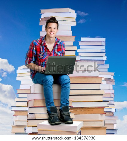 Young man sitting on a stack of books with a laptop,outdoors
