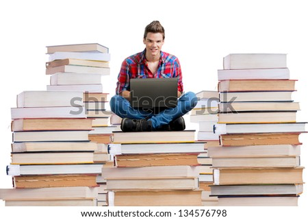 Young man sitting on a stack of books with a laptop,white background - stock photo