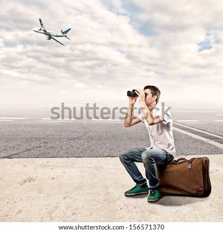 young man sitting on a suitcase and using binoculars at the airport - stock photo