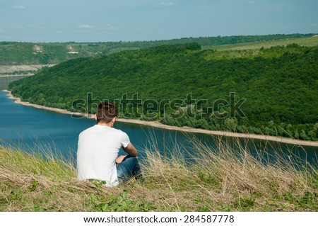 Young man sitting on a top of a mountain viewing wide river - stock photo