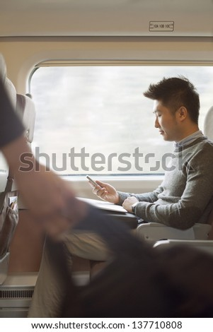 Young man sitting on a train using his phone - stock photo
