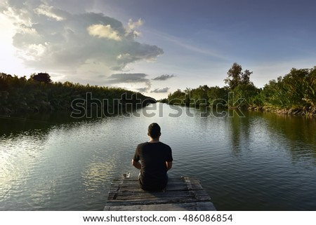 Young man sitting on a wooden bridge alone during blue sky