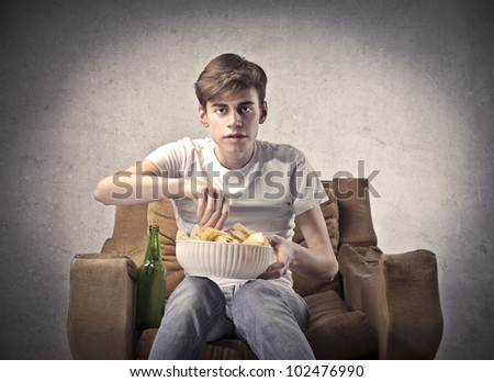 Young man sitting on an armchair with a beer beside him and a bowl of chips on his knees - stock photo