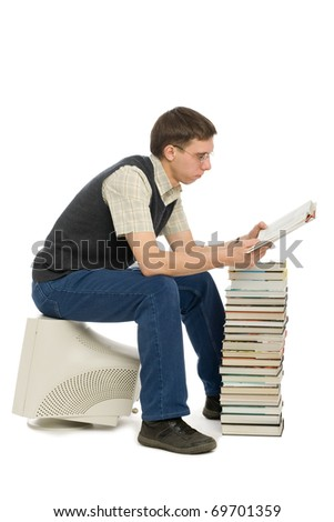 Young man sitting on an old monitor and reads a book. Book instead of a computer.
