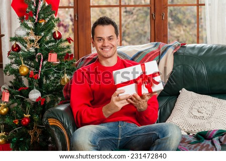 Young man sitting on couch, alone, in front of christmas tree on living room,holding a gift box. - stock photo