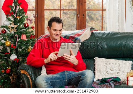 Young man sitting on couch, alone, in front of christmas tree on living room,using tablet pc. - stock photo