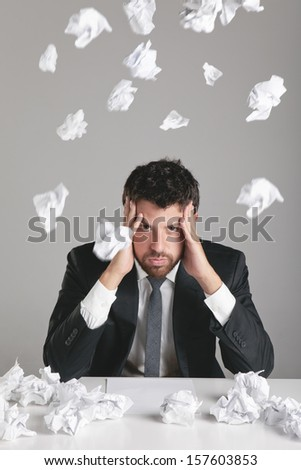 Young man sitting on desktop with papers flying around./ Portrait of a young businessman with headache.
