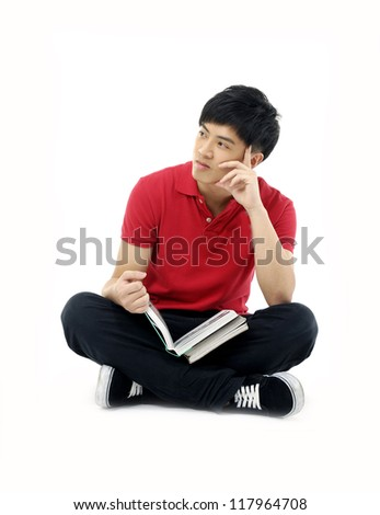 Young man sitting on floor and reading a book, isolated on white background - stock photo
