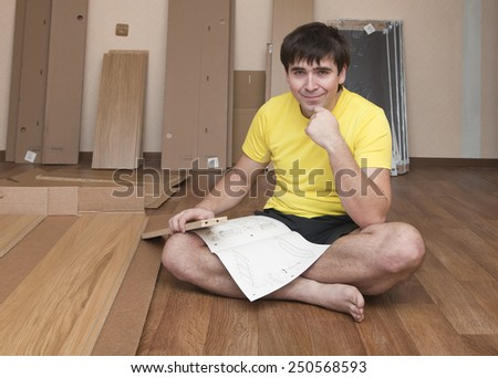 Young man sitting on floor assembling flatpack closet