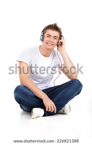 young man sitting on floor listening to music looking into camera. Guy sitting on floor and listening music on white background - stock photo