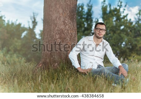 Young man sitting on grass against a tree. Handsome guy repose in nature. Outdoors - outside. Full body - stock photo