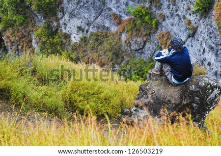 Young man sitting on mountain rock by the cliff
