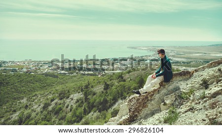 Young man sitting on peak of mountain and enjoying view of sea in summer - stock photo