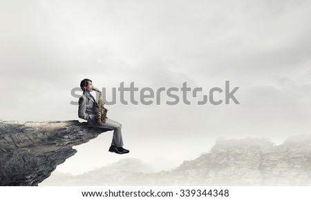 Young man sitting on rock edge playing saxophone