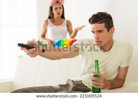Young man sitting on sofa and watching tv. His angry wife yelling. - stock photo