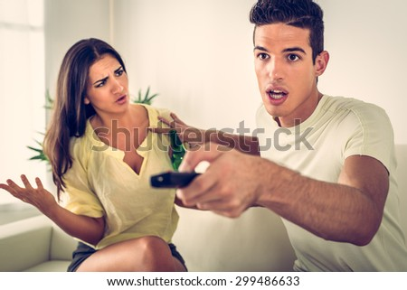 Young man sitting on sofa and watching tv. His angry wife yelling.