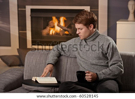 Young man sitting on sofa at home on a cold winter day, reading book in front of fireplace.