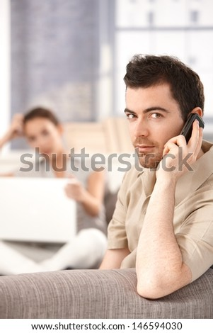 Young man sitting on sofa at home, talking on mobile, woman using laptop in the background. - stock photo