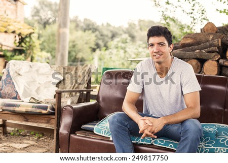 Young man sitting on sofa in rural scene. - stock photo