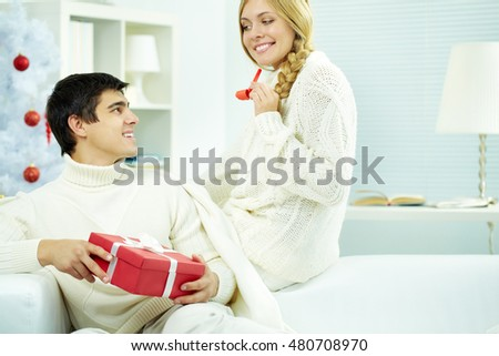Young man sitting on sofa with a gift box and looking at his wife