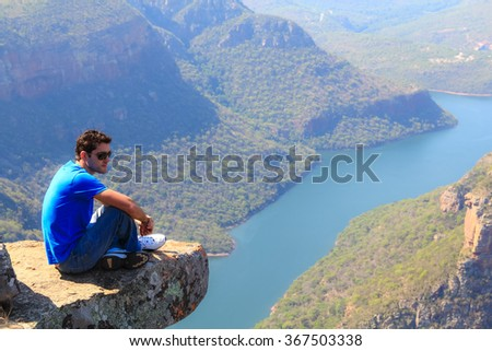 Young man sitting on stone on the cliff in the Blyde River Canyon, South Africa - stock photo
