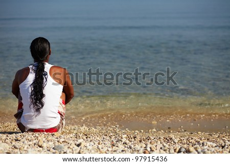 Young man sitting on the beach enjoying peaceful moment