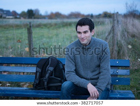 young man, sitting on the bench at evening time, dusk
