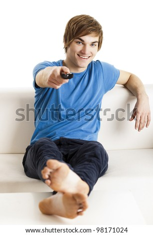 Young man sitting on the couch using a remote control - stock photo
