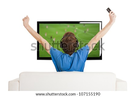 Young man sitting on the couch watching a football game on tv with arms up - stock photo