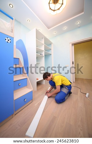 Young man sitting on the floor secures door sliding wardrobe in room with blue walls - stock photo