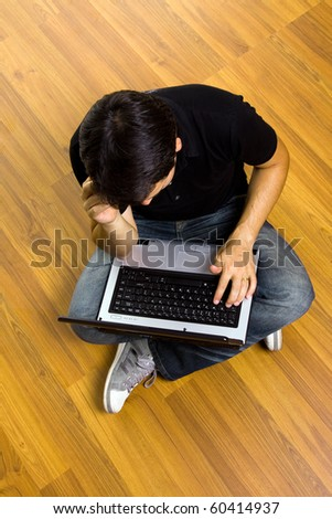 young man sitting on the floor working on laptop computer at home - stock photo
