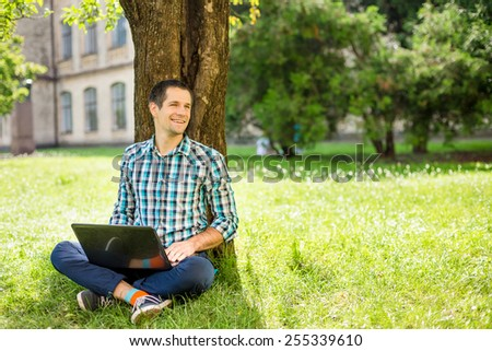Young man sitting on the grass and working on laptop
