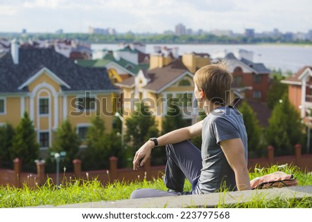 Young man sitting on the grass dreaming about his own house. Urban landscape with village  - stock photo