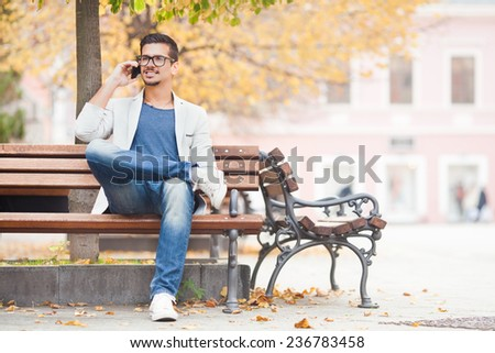 Young man sitting on the park bench talking on the mobile phone - stock photo