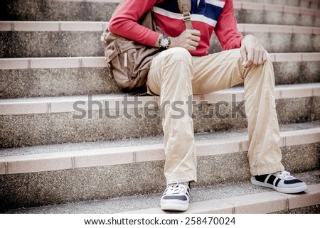 young man sitting on the stairs - stock photo