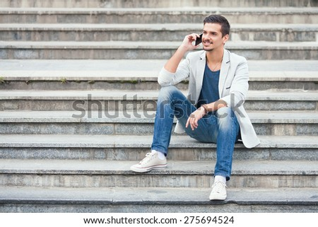 Young man sitting on the stairs talking on the mobile phone - stock photo