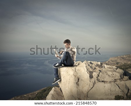 young man sitting on the top of a rock reading a book - stock photo