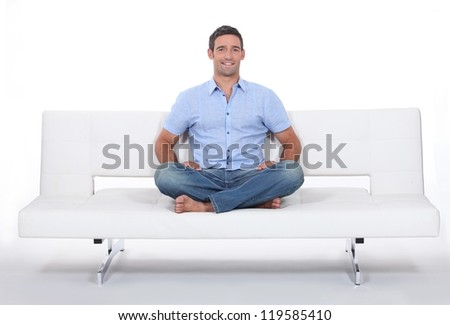 Young man sitting on white sofa