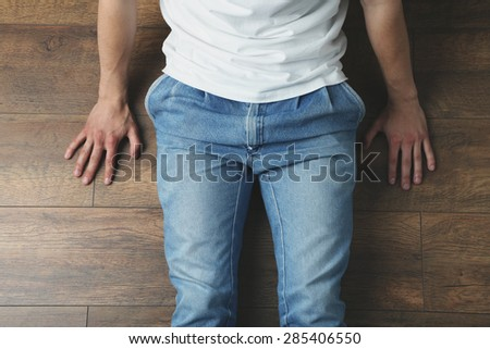 Young man sitting on wooden floor in room