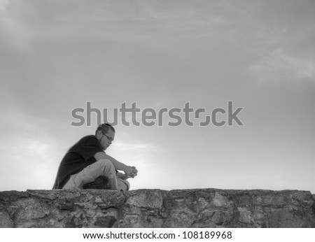 Young man sitting outdoors and meditating - stock photo