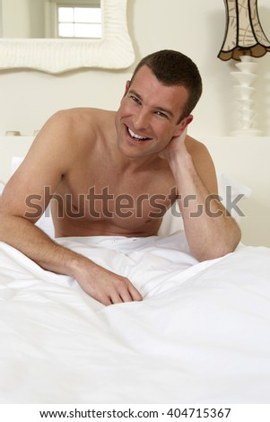 Young man sitting up in bed, laughing