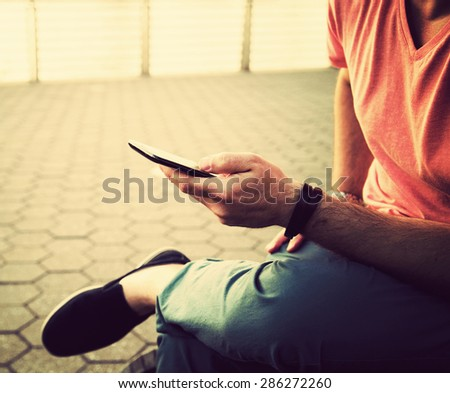 Young man sitting using a smart phone, Dressed casually. Flare light and vintage post processed. Urban life style, technology, online, business, shopping, fashion and job hunting concept.
