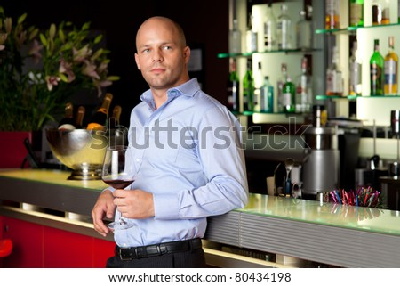 young man sitting, waiting with glass of whine next to the bar - stock photo
